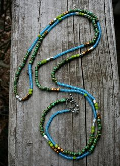 Measuring just over 43 inches, this awesome multi-purpose strand can be worn as a long boho style necklace alone or layered, doubled or as a bracelet wrapped five or six times! Made of: -lovely earthy turquoise picasso hybrid seed beads  -sky blue seed beads  -golden glass cube beads  -lime green glass cube beads  -Bali sterling silver rectangular beads    Finished with a silver toggle clasp and pretty silver flower charm. Thank you for looking!  please see my shop for much more http:/&#...