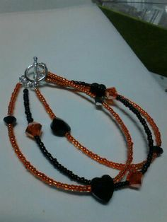 black and orange tri bracelet made with seed beads and swarovski black heart beads...for sale