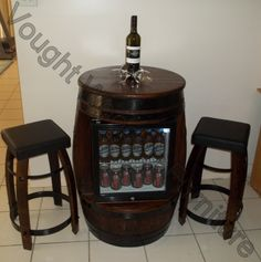 Wine barrel table with a glass door fridge built into it.  2 stools made from parts of wine barrel staves, rings & steel.  http://voughtwoodenfurniture.id.au/wine-barrel-with-bar-fridge/4580541565