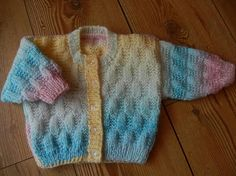 This lovely baby cardigan/sweater has been hand knitted using lovely soft baby acrylic yarn in shades of green, pink, lemon, blue. It has been knitted using a block stitch design. It has been finished with 5 buttons.  0-6 month  chest measures 18  All items are from a non smoking home.  All items are ready for next day dispatch  I will combine postage for multiple purchases, just message me before buying so I can adjust the postage cost x  Please read my shop policies for more informatio...