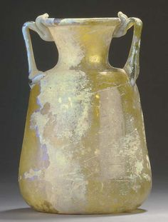A ROMAN GLASS AMPHORA  CIRCA LATE 1ST-EARLY 2ND CENTURY A.D.  Honey gold in color, free-blown, with a tapering cylindrical body, rounded shoulders and flaring neck, the rim folded out then in, on a concave base, with twin vertical handles  7 in. (17.8 cm.) high