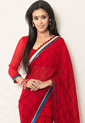 Try out this year top trend, glowing, bold and natural collection. This red faux georgette saree is nicely designed with check print, lace and graceful patch border. Saree gives you a singular and dissimilar look. Matching blouse is available. Slight color variations are possible due to differing screen and photograph resolution.