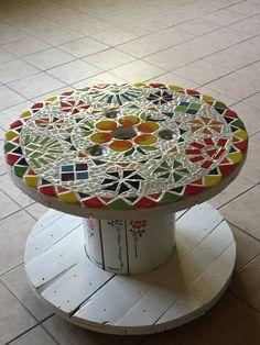 Rollo de cable transformado en mesa para el patio con técnica vitro- mosaiquismo . Y stensil  en el tronco de la mesa.