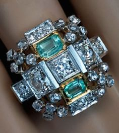Art Deco Vintage Cocktail Ring  circa 1935  This large geometric ring is designed as a cross shaped stylized pyramid with a flat top set with two emerald cut green beryls and old European cut diamonds,   surrounded by four rose-cut diamond clusters.  The ring is handcrafted in white and yellow gold.  Estimated total diamond weight 2.30 ct.