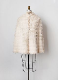 Vintage 1960s white faux fur tiered capelet. Lined in satin with cut outs for arms and three frog button closures down the front.  SIZING Fits like: