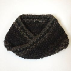 This textured neck warmer was hand-knit in a moebius infinity loop using wool yarn. The knitting technique adds a subtle texture and the dark neutral tones for a versatile, classic accessory.