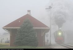 Through the fog. Iowa Interstate's doubleheaded 2-10-2s emerge from the fog and blast past the former Rock Island station in Wilton with a manifest freight. The Chinese imports were on their way to Rock Island for a weekend of flood relief trains.