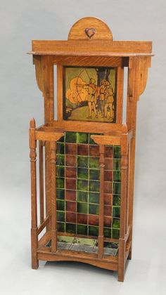 British arts & crafts quartersawn oak hall stand, the arched crest with ceramic heart inset above a polychrome panel depicting Robin Hood, glazed tile back flanked with umbrella holder, retaining tray, 58''h x 30''w x 12''d
