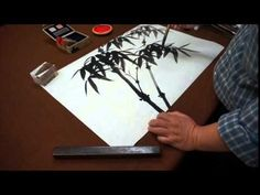 How to load the brush and paint bamboo leaves in black ink.