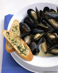 This dish is based on classic moules mariniere, with a bit of cream added. Be sure to discard any unopened shells after steaming, and serve with crusty bread to sop up the sauce.