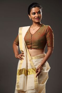 Kaapi Niram` Embroidery Blouse – Seamstress A coffee brown blouse embroidered with motifs in yellow, green and brown. Printed edging adds to the allure. Kerala Saree Blouse Designs, Blouse Neck Designs, Blouse Patterns, Beautiful Blouses, Beautiful Saree, Indian Dresses, Indian Outfits, Kasavu Saree, Sarees