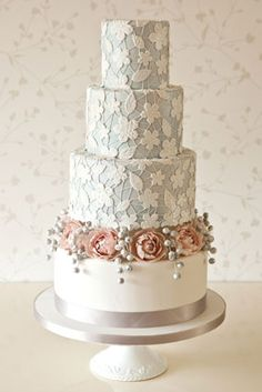 A silvery lace effect adorns the top three tiers of this cake with a pretty divide of sugar peonies.