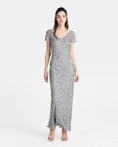 Vestido largo en color gris plata con trabajo de lentejuelas en toda la prenda. Tiene manga corta, escote en pico y cierre de cremallera en la espalda.