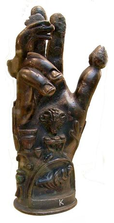 """""""Main de Sabazios"""" - Sabazios est un dieu thrace ou phrygien qui apparaît à Athènes vers le Ve siècle avant notre ère. Son principal attribut est le serpent. Son culte à mystère semble être en rapport avec celui de la """"Magna Mater"""", la Grande Mère. À l'époque romaine impériale, il est assimilé à Bacchus ou Jupiter. Son culte initiatique, comportait une procession au cours de laquelle les fidèles dévêtus portaient un serpent, ou une main décorée de références à l'animal."""