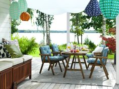 Wooden table and chairs with blue and white seat cushions on a colorful outdoor terrace overlooking a lake.