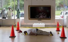 Two men look through a window at an art installation depicting the body of Michael Brown, made by artist Ti-Rock Moore, at Gallery Guichard in Chicago on July 14, 2015