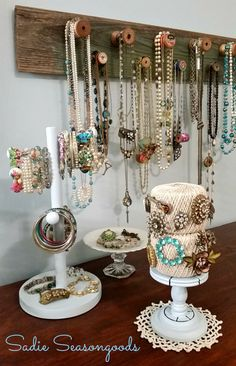 An old board with old spools nailed on holds necklaces, an antique candy dish holds assorted baubles...