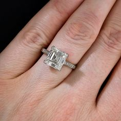 This astonishingly beautiful, original Edwardian diamond ring, circa 1910, gleams with a gorgeous square step-cut, or Carré cut (an emerald-cut, diamond without cut corners), accompanied by a GIA - Gemological Institute of America grading report stating: J color - VVS2 Clarity. The diamond is elegantly presented in a stately, finely handcrafted platinum setting with a geometric (early-Art Deco) gallery with tiny twinkling diamonds set down the shoulders and enlivening the the four 'V'...