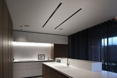 Corian kitchen lit by Kreon recessed LED double focus linear NUIT profiles.