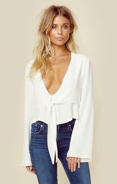 """Flynn Skye's London Lace Top features long bell sleeves, front tie accent, ruffled hem, and lace paneling in the back. Made in USADry Clean Only100% RayonFit Guide:Model is 5ft 7 inches; Bust: 32"""", Waist: 24"""", Hips: 34""""Model is wearing a size XSRelaxed FitShoes Featured Not Available For Purchase"""