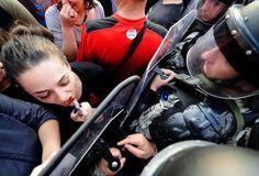 Manifestante macedônio passa batom usando o protetor do motim da polícia como um espelho :)