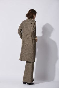 Andrew Coat: Virgin wool coat with tweed print in beige and brown. It has a crew neck and Japanese sleeves. The coat is buttonless and has pockets on the sides and it is lined in stretch silk satin. Made in Barcelona. Cortana AW 2016 collection.