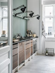 Wooden pull-out kitchen drawers with contrasting cabinetry. Task lamps as kitchen lighting. Nice muted emerald green wall.