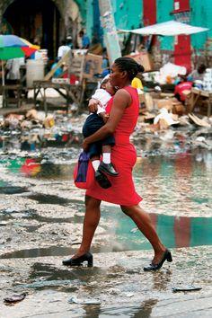 Une femme et son enfant marchant à grand pas pour échapper à l'averse. Port au Prince, Haïti.