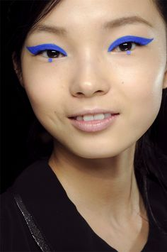 """Pat McGrath adds azure to Anna Sui Fall 2012.    """"You draw your shape, fill it in, and add your shadow,"""" McGrath said, demoing the process on the back of her hand with CoverGirl Liquiline Blast Eyeliner in Blue Boom and its Eye Enhancers 1-Kit Shadow in Indigo Impact. Tracing inner rims with a white pencil to open the eye, McGrath added a few coats of CoverGirl LashPerfection mascara for a dramatic sixties feel."""