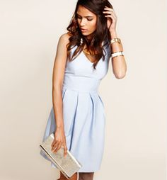 MODEL WEARING A PALE BLUE SLEEVELESS DRESS AND HOLDING A SILVER CLUTCH.