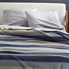 Wool-blend blanket stripes the bed in navy, grey and orange. A modern, lighter-weight version of the classic camp style, cover is perfect as a go-to throw or lining the foot of the bed.
