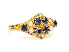 Victorian Antique Sapphire & Pearl Ring: A full set of English hallmarks adds even more allure and history to this delightful Victorian yellow gold ring of 9k. English feminine charm fans out across a lozenge shaped matrix studded with six (6) oval faceted natural sapphires and six natural half seed pearls (untested but assumed natural due to age and examination) all claw set in a textured golden expanse.      Date: 1885.