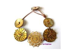 Bracelet button jewelry made of vintage metal filigree flowers shell buttons on leather cord from oritdotan on etsy.  If you like vintage buttons to redo a piece of clothing or make jewelry you will love this store.
