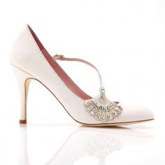 The ultimate in 1920's, 30s style glamour, The Elizabeth has a beautiful round toe shape. The bridal shoe made in ivory kid suede and metallic silver leather has a flatteringly low cut with an asymmetric diagonal strap and stunning deco inspired pearl and crystal fan trim. The ivory suede can be dyed after your wedding to give your shoes a whole new lease of life. Emmy Scarterfield is the innovative designer behind the brand. She has worked for many of the most influential fashion houses in…