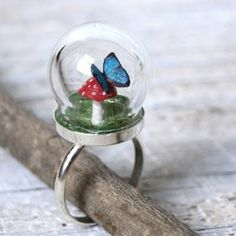 Safely housed under a tiny, sturdy glass globe, a delicate blue morpho butterfly rests on a red spotted mushroom. A part of Tiny Terrarium series by Mai McKemy.  >> Woodland Belle Tiny Woodland Terrarium Toadstool Mushroom and Blue Morpho Butterfly Ring [Etsy]