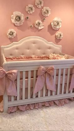Elegant DIY paper roses and satin bows on a crib with tufted upholstery and dupioni silk baby bedding with ruffles.  Pink baby girl nursery decorating ideas with DIY crafts projects.