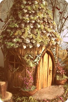 a cute house made of  a stump with pinecone roof and hand carved door