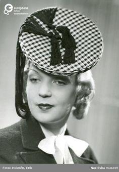 Porträtt av kvinna i rutig hatt med svarta tofsar från Madame Suzy b85ca35ea5a2a