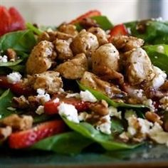 Fresh spinach leaves are topped with crumbled goat cheese, strawberries, candied pecans, and savory chicken breast meat in a salad that works as either a side dish, lunch, or a light supper.