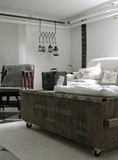 Note to self: Instead of a coffee table, this is inspiration for an industrial porch seat---old shipping crate on casters + cushions.