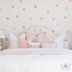 Coral pink watercolour polka dot wall decals placed as a pattern on a beige wall in a bedroom. Each polka dot features a distinct circle shape with slightly accentuated curves and a beautiful pastel pink color.