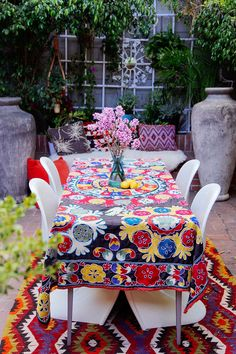 Dining al fresco is the only way to go in the summers, yes? Use a colorful suzani blanket as a tablecloth to create an instant festive-feel.  @airbnb