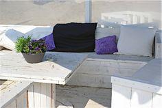 Bank met gezellige kussens op het terras van strandpaviljoen Zee