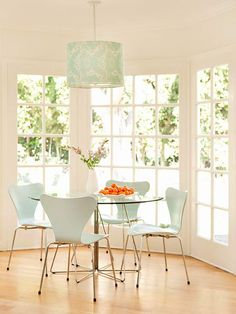 Love the freshness of the color palette!  I could drink coffee in this nook for a lifetime.  Consistency Is Key In the breakfast dining area, the chairs carry the aqua hue from the adjacent family room, and their modern lines blend perfectly with a sleek glass tabletop. A drum shade hanging above the table is wrapped in patterned fabric that repeats in the kitchen's window treatments