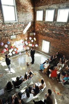 White and various color balloons against a black theater curtain back drop during ceremony. Yeah?