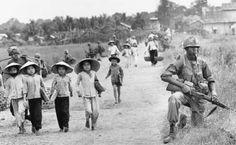 Dec.1965 - women and children, holding hands, tentatively walk by a US soldier near Xuan Dien. Photo by Horst Faas AP ~ Vietnam War