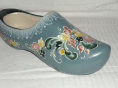 This lovely rosemaled handmade wooden shoe measures 9.5 long and is 3 wide. It is backgrounded in Norwegian Blue and rosemaled with English Red, Light Cadmium Yellow and Prussian Blue. The quaint Norwegian Clog is handmade and its Telemark Style pattern is original. There is a small hanger on the base of the heel for displaying on your wall or it can rest on a shelf or desktop for easy viewing.