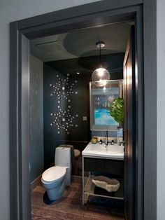 This gray powder room with wood floors features a bold, glass ball pendant light and graphic metal wall art that offer a contemporary touch.