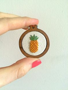 Bring a bit of tropical sunshine to everyday with this embroidered pineapple!  The pineapple is hand embroidered on 100% natural cotton calico.  The embroidery is then mounted in a tiny handmade wooden hoop frame which measures just 4cm (1.5) and finished with either a 43cm (17) silver plated chain or a brooch back.  This mini hoop would be the perfect gift and is perfect for holidays or festivals.  I also have super cute teeny cupcake, watermelon and donut designs available here…
