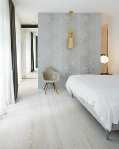 an old Berlin factory becomes a modern city home-modern take on wood floors-wide plank but with whitewash finish that works so well with the concrete wall, grey white, greige then the brass light fixture-so many layers to this room